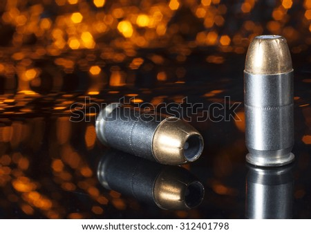 Two handgun cartridges that have hollow point bullets with an orange background - stock photo