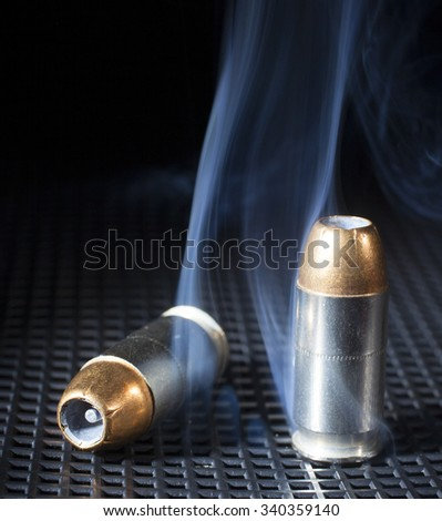 Two handgun cartridges with hollow point bullets and smoke - stock photo