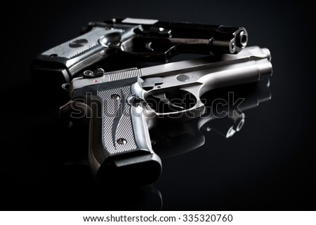 two handguns on black background - stock photo