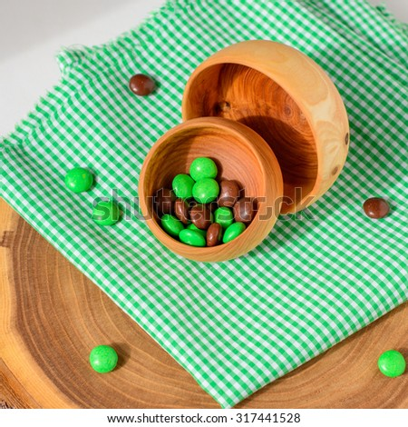 two handmade wooden bowls with colorful sweets on wooden background - stock photo
