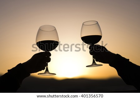Two Hands and wineglass silhouette on sunset. - stock photo
