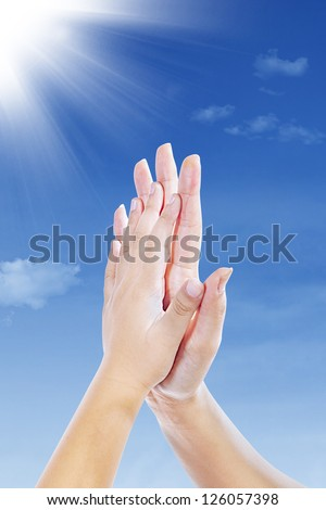 Two hands clap together under blue sky - stock photo