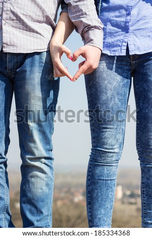 Two hands coming together to create a heart