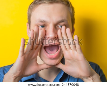 Two hands covering her mouth on the sides show a loud cry. young guy on a yellow background. Photo. Men loudly calling someone. - stock photo