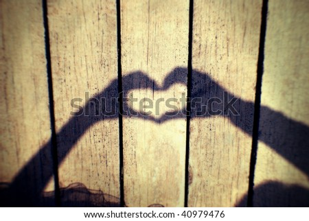 two hands forming a heart shadow - stock photo