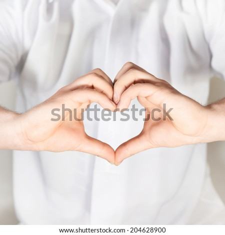 Two hands gesture forming a heart shape against the white shirt, shallow depth of field - stock photo