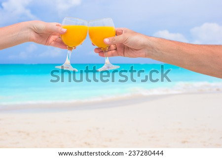 Two hands hold glasses with orange juice background blue sky - stock photo