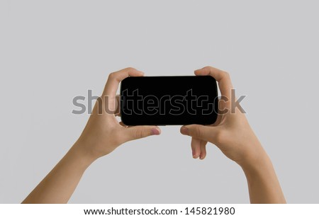 Two hands hold the phone in a horizontal position - stock photo