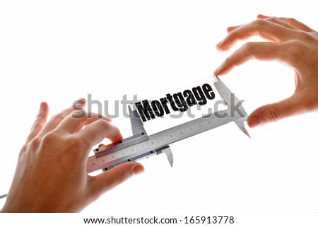 """Two hands holding a caliper, measuring the word """"Mortgage"""". - stock photo"""