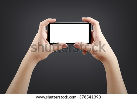 Two hands holding big screen smart phone, isolated on dark background, clipping path - stock photo