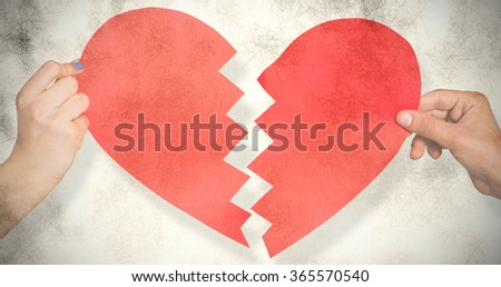 Two hands holding broken heart against grey background - stock photo