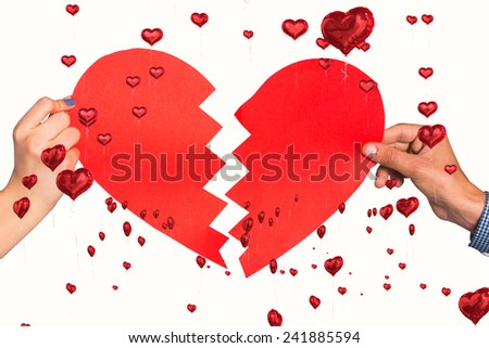 Two hands holding broken heart against red heart balloons floating - stock photo