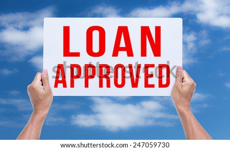 Two hands holding brown cardboard with loan approved on blue sky background - stock photo