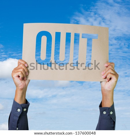 Two hands holding brown cardboard with quit overhead on blue sky background - stock photo