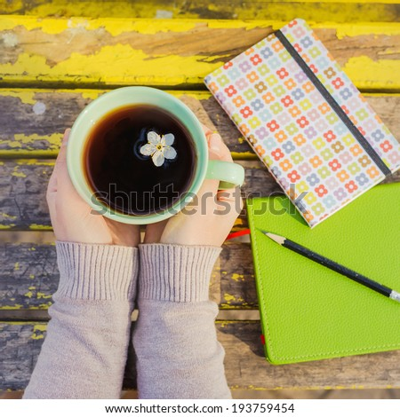 Two hands holding chamomile tea in a cup on wooden background - stock photo