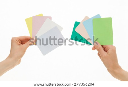 Two hands holding colorful paper cards, white background - stock photo