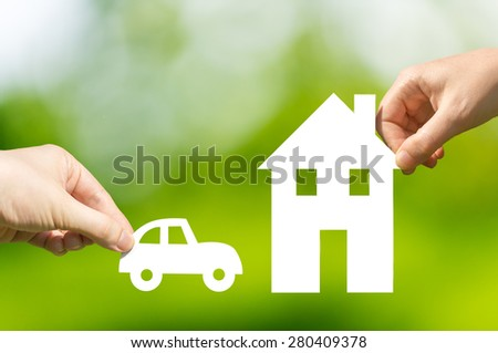 Two hands holding cut out paper car and house
