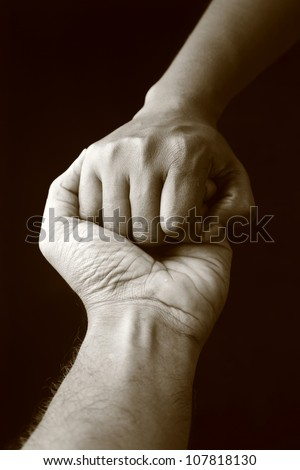 Two hands holding each other in a dark background - stock photo