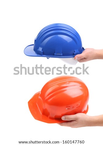 Two hands holding hard hats. Whole background. - stock photo