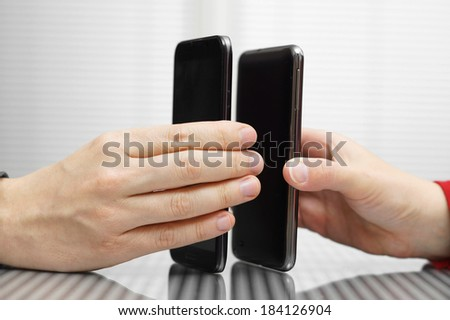 Two hands holding mobile smart phones while transferring data - stock photo