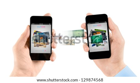 Two hands holding mobile smartphones while transferring pictures from one smart phone to another. - stock photo
