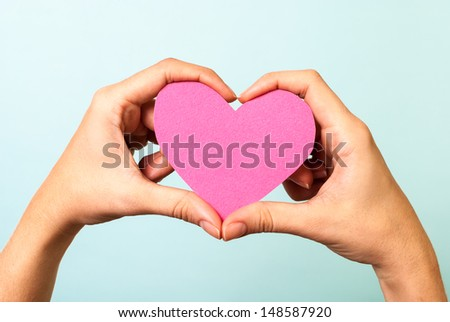Two hands holding/showing a pink lovely heart shape, on blue background. Love concept. - stock photo