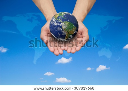 Two hands holding the earth on blurred map over beautiful blue sky backgrounds.Elements of this image furnished by NASA.safe and healing world concept.  - stock photo