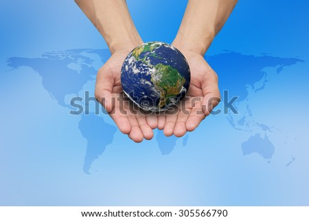 Two hands holding the earth on blurred map over blue sky backgrounds.Elements of this image furnished by NASA.safe and healing world concept. - stock photo