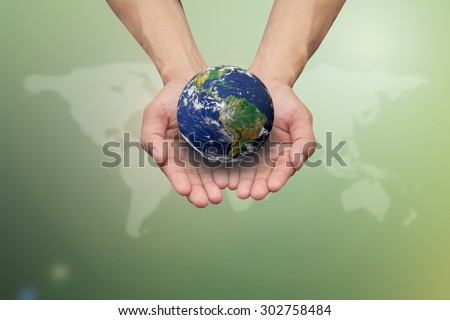 Two hands holding the earth on blurred map over green nature backgrounds.Elements of this image furnished by NASA.safe and healing world concept. - stock photo