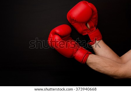 Two hands in red boxing gloves in the side of the frame on a black background