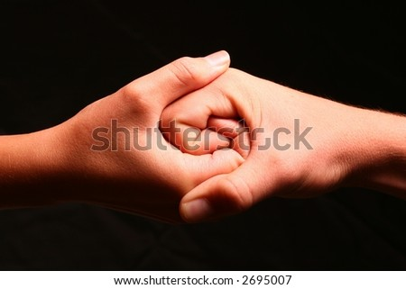 Two hands intertwined to create a Jinn Jan type symbol signifying unity and strength