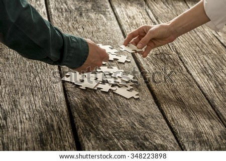 Two hands, male and female, matching two puzzle pieces over a pile of other pieces lying on a textured rustic wooden desk. Conceptual of teamwork and overcoming problems and challenges. - stock photo