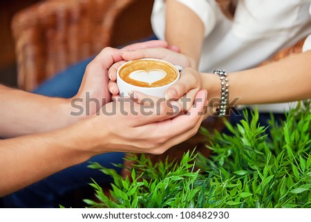 two hands - man's and female hold one cup of coffee with heart drawing. man's hands embrace female hands. Concept of friendship, love, relations, valentine - stock photo