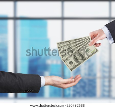 Two hands, money transferring process. Dollar bills. Business city view on the background form the panoramic windows of the modern office. - stock photo