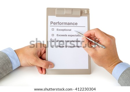 Two hands of a businessman with suit holding a clipboard with a performance checklist and a silver pen