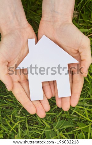 Two hands of a Caucasian woman holding a white cutout house over green grass, top view.