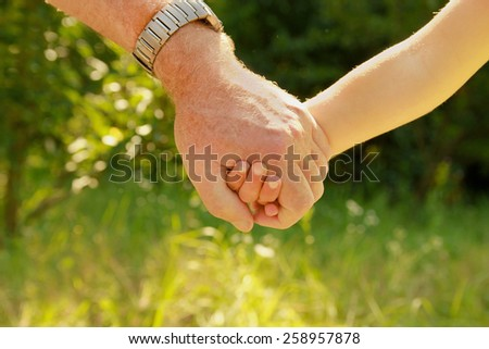 two hands of an elderly couple and child - stock photo