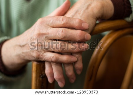 two hands of an elderly woman sitting on a chair - stock photo
