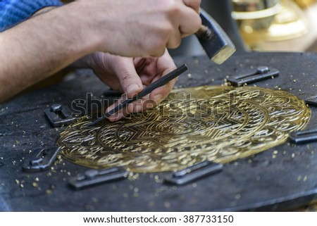 Two Hands of Craftsman Engraving Brass Plate Masterpiece - stock photo