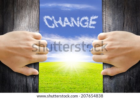 Two hands opening old wooden door to the new world. Change concept. - stock photo