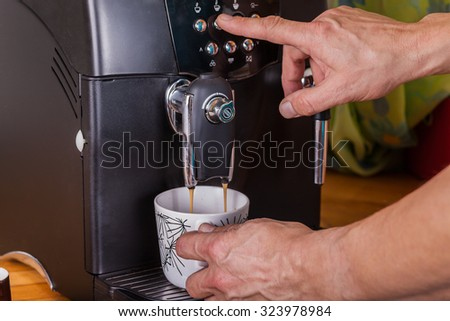 Two hands operate at a coffee machine