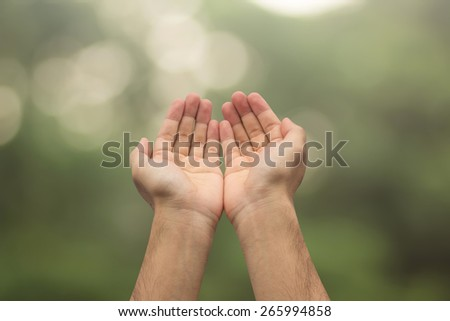 Two hands pray on blurred nature background , soft focused. - stock photo