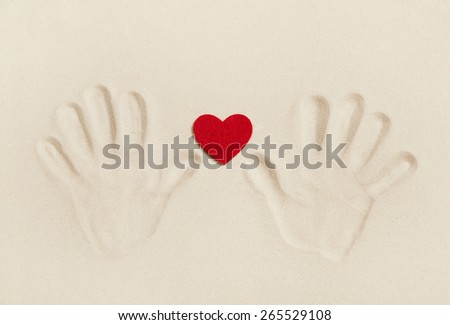 Two hands print in the sand with a red heart. Symbol concept for love, togetherness, friendship or vacation on the beach. - stock photo