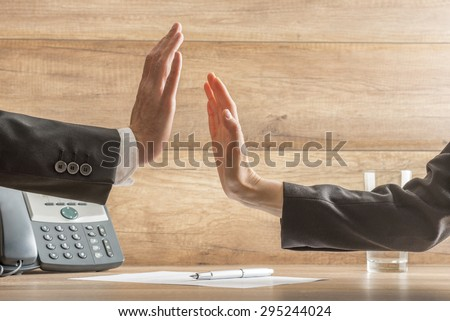 Two hands reach to hi-five across business table in order to celebrate a successful business deal, arms in black suits, telephone, document with pen and glass of water visible, wooden background. - stock photo