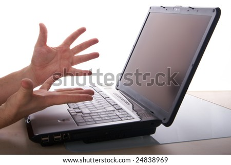 Two hands show anger towards a laptop Computer on a table with white background.