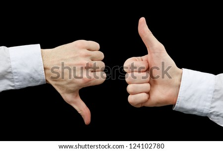 Two hands showing different gestures. Thumb up and thumb down on black background - stock photo