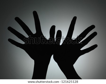 two hands silhouette with fingers spread backlit on grey gradient background