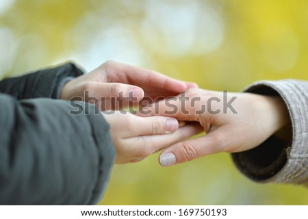 Two hands together against the fallen leaves