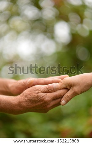 Two hands together against the green natural background - stock photo