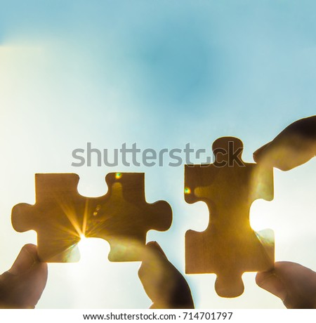 two hands trying to connect couple puzzle piece with sunset background. empty space. Jigsaw wooden puzzle against sun rays. two part of whole. symbol of association and connection. business strategy